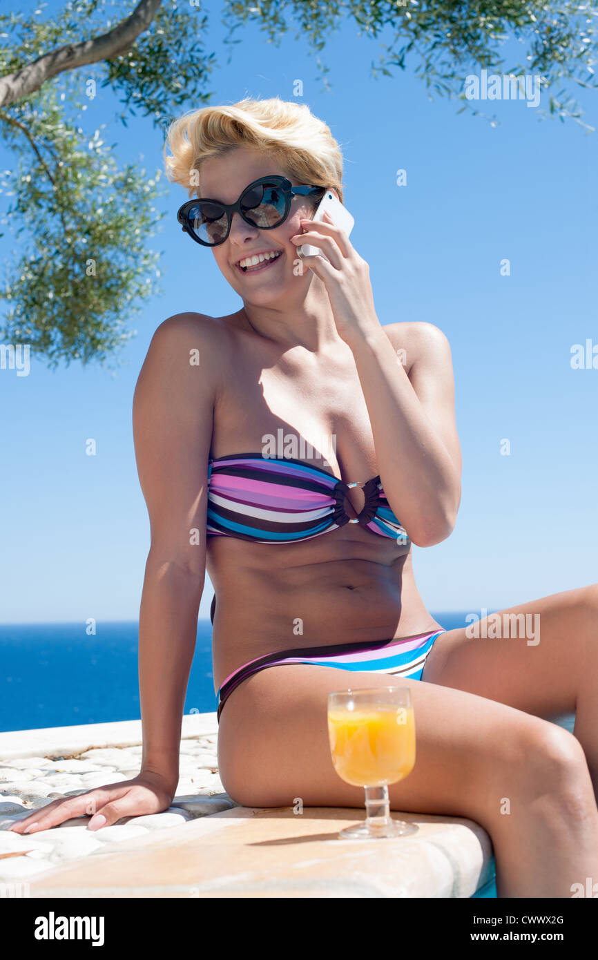 Woman talking on cell phone by pool - Stock Image