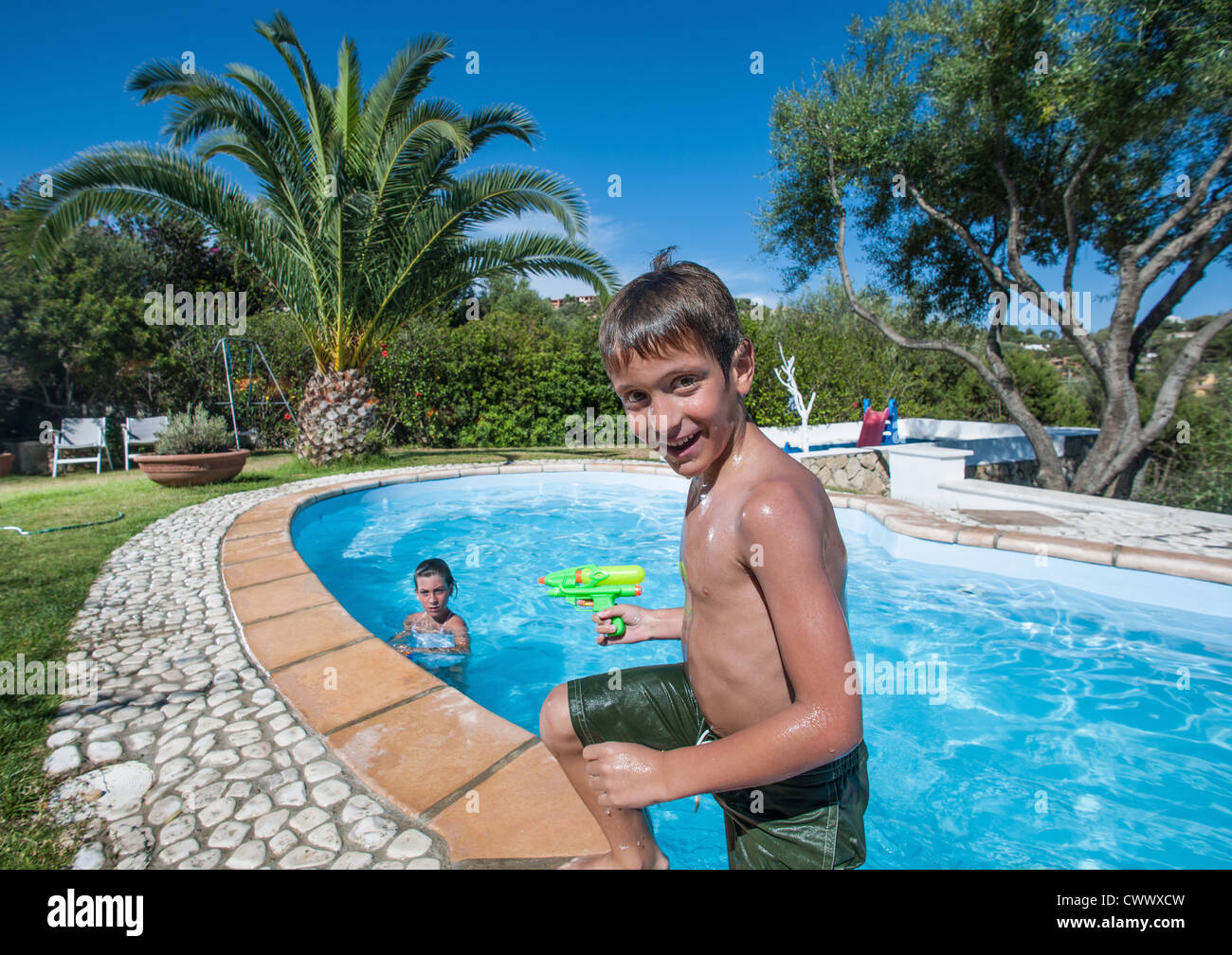 Boy climbing out of outdoor pool - Stock Image