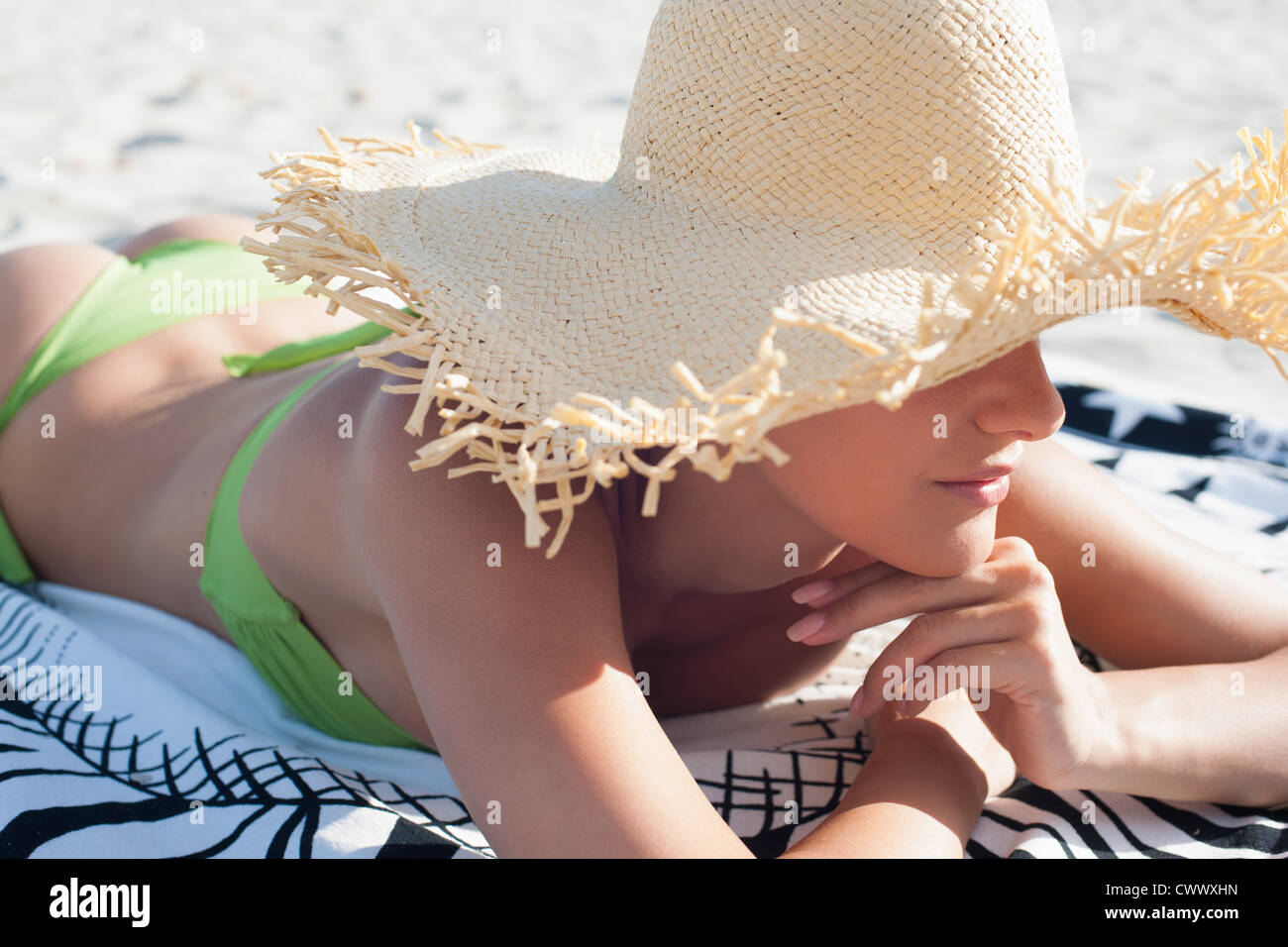 Woman wearing straw hat on beach - Stock Image