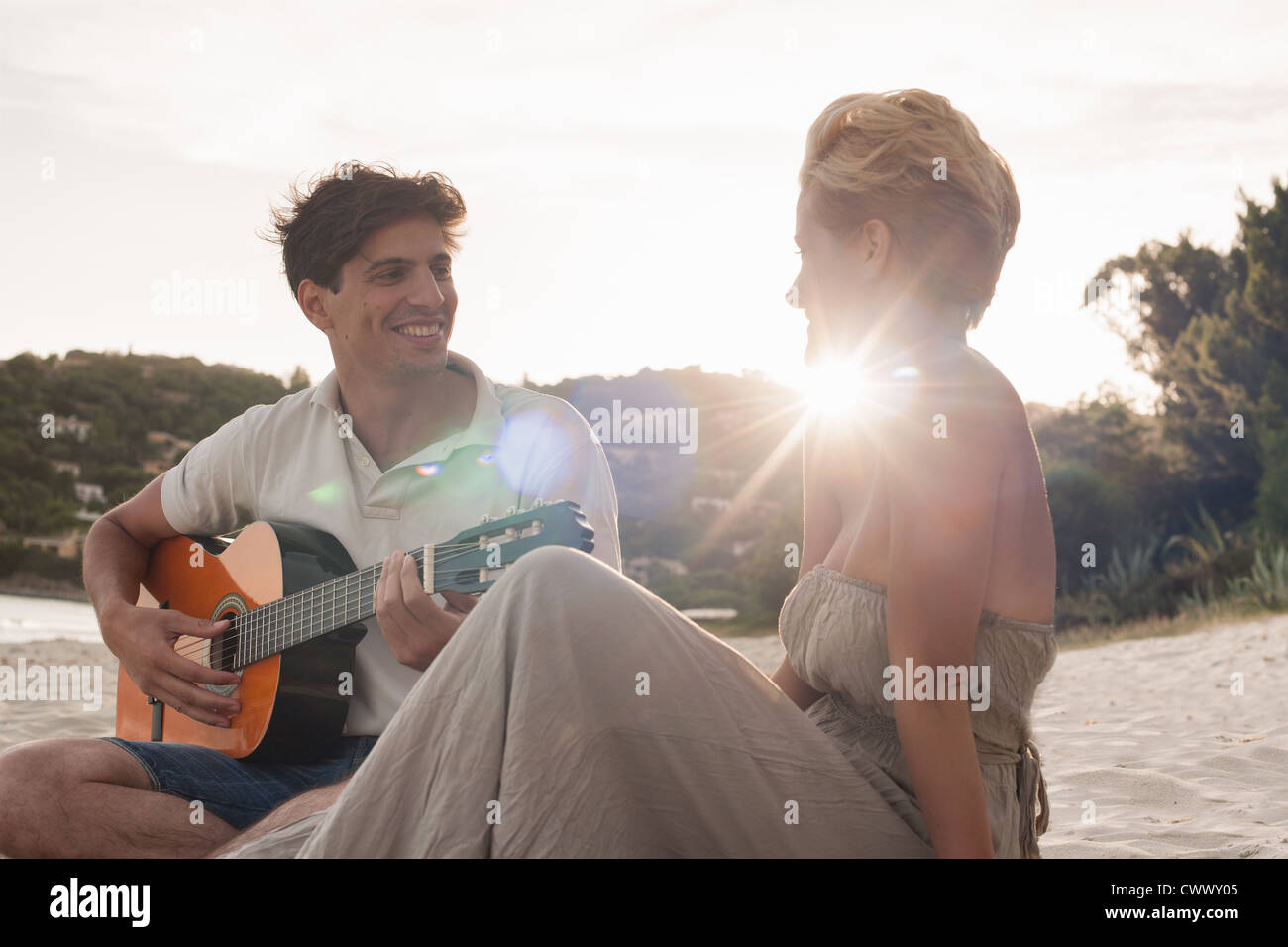 Man playing guitar for girlfriend - Stock Image