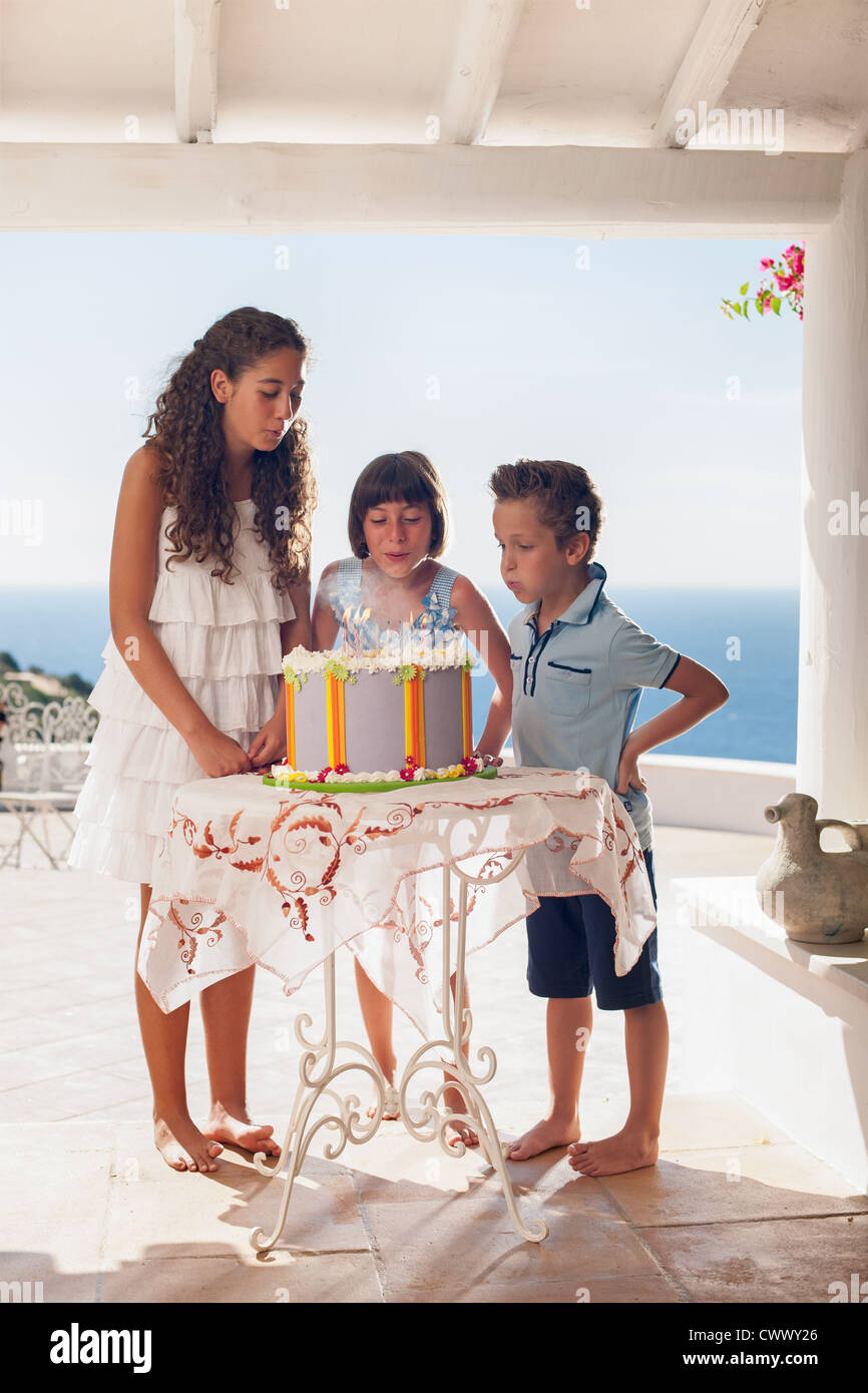 Children blowing out birthday candles Stock Photo