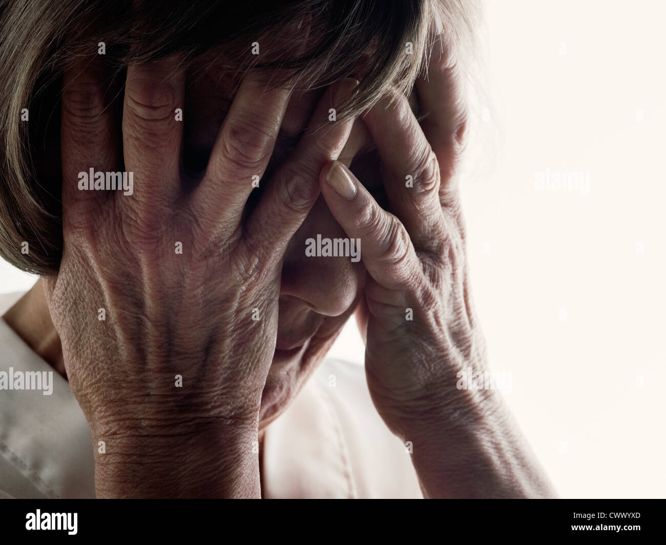 Older woman clutching her face - Stock Image