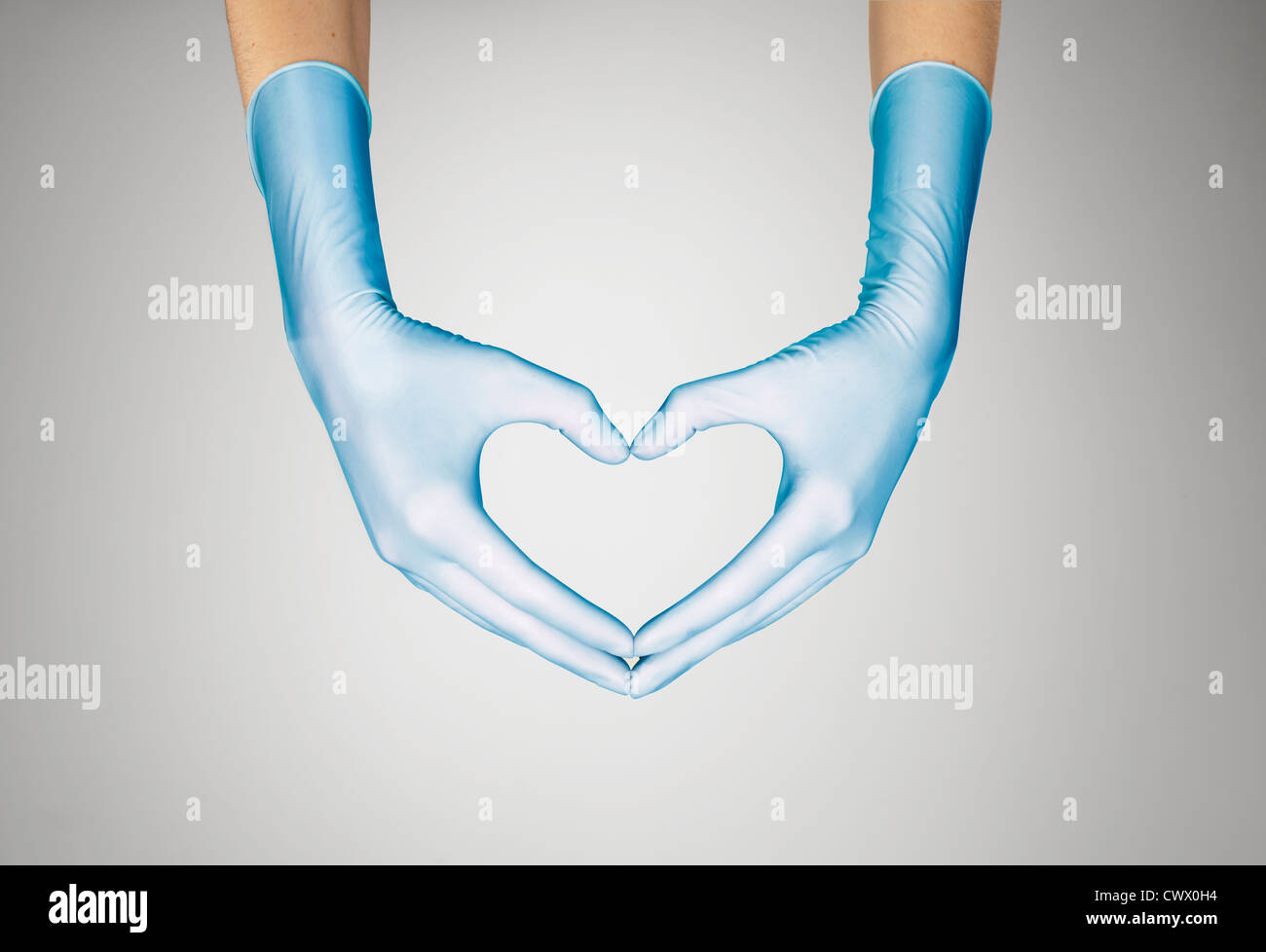 Gloved hands making heart shape Stock Photo