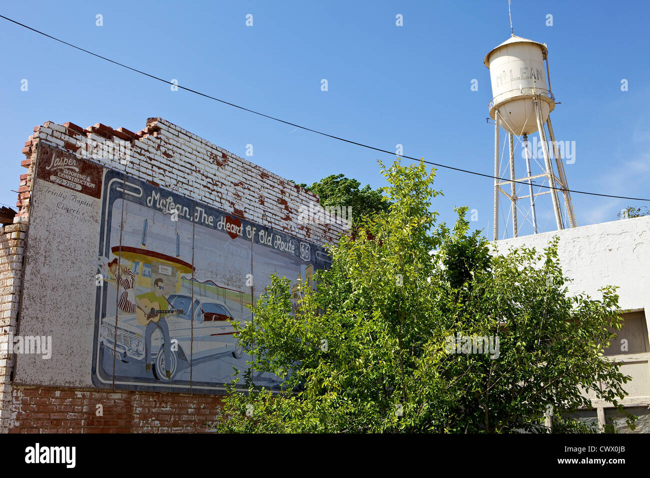 Faded mural on a crumbling wall with a water tower in the background along Route 66 in McLean, Texas - Stock Image