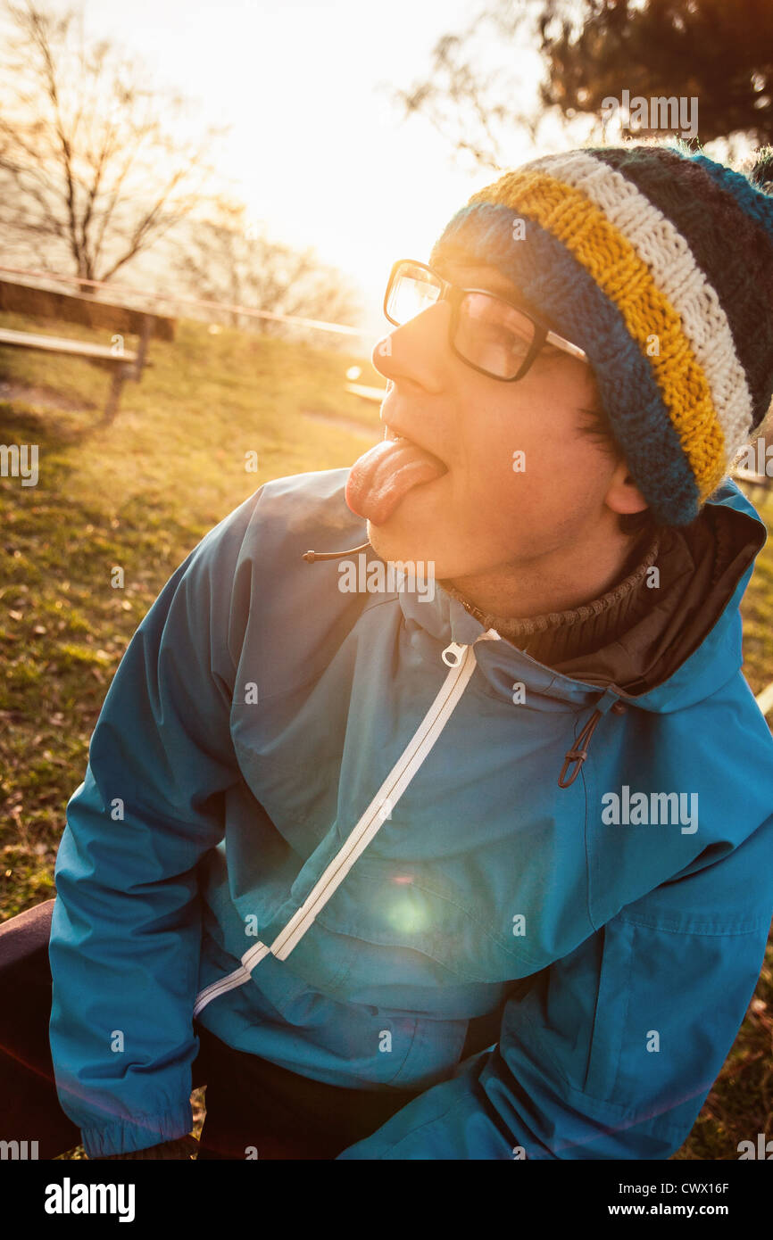 Man sticking his tongue out outdoors - Stock Image