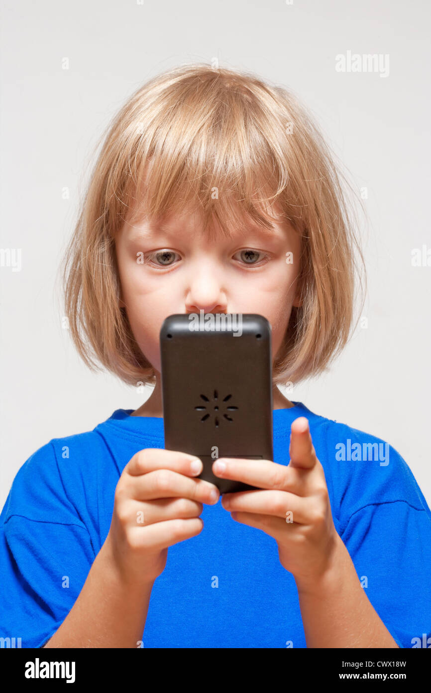 boy playing with handheld computer game - isolated on light gray - Stock Image