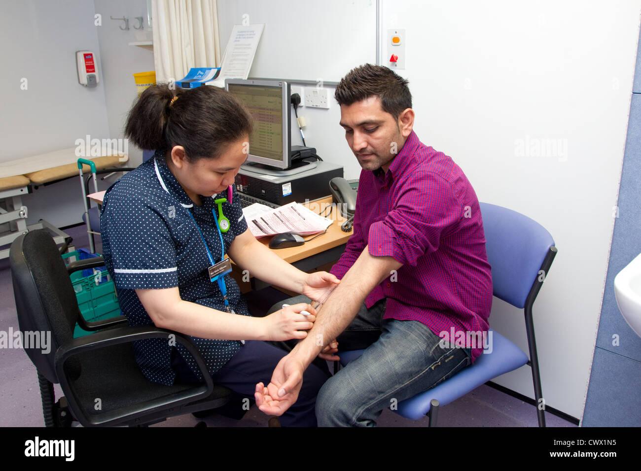 Nurse measuring positive result of TB test - Stock Image