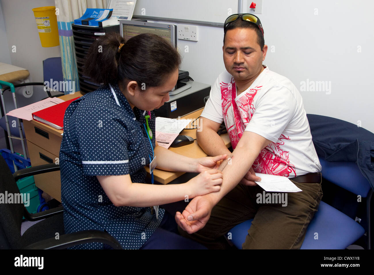 Nurse measuring scab for positive result of Tuberculosis test - Stock Image
