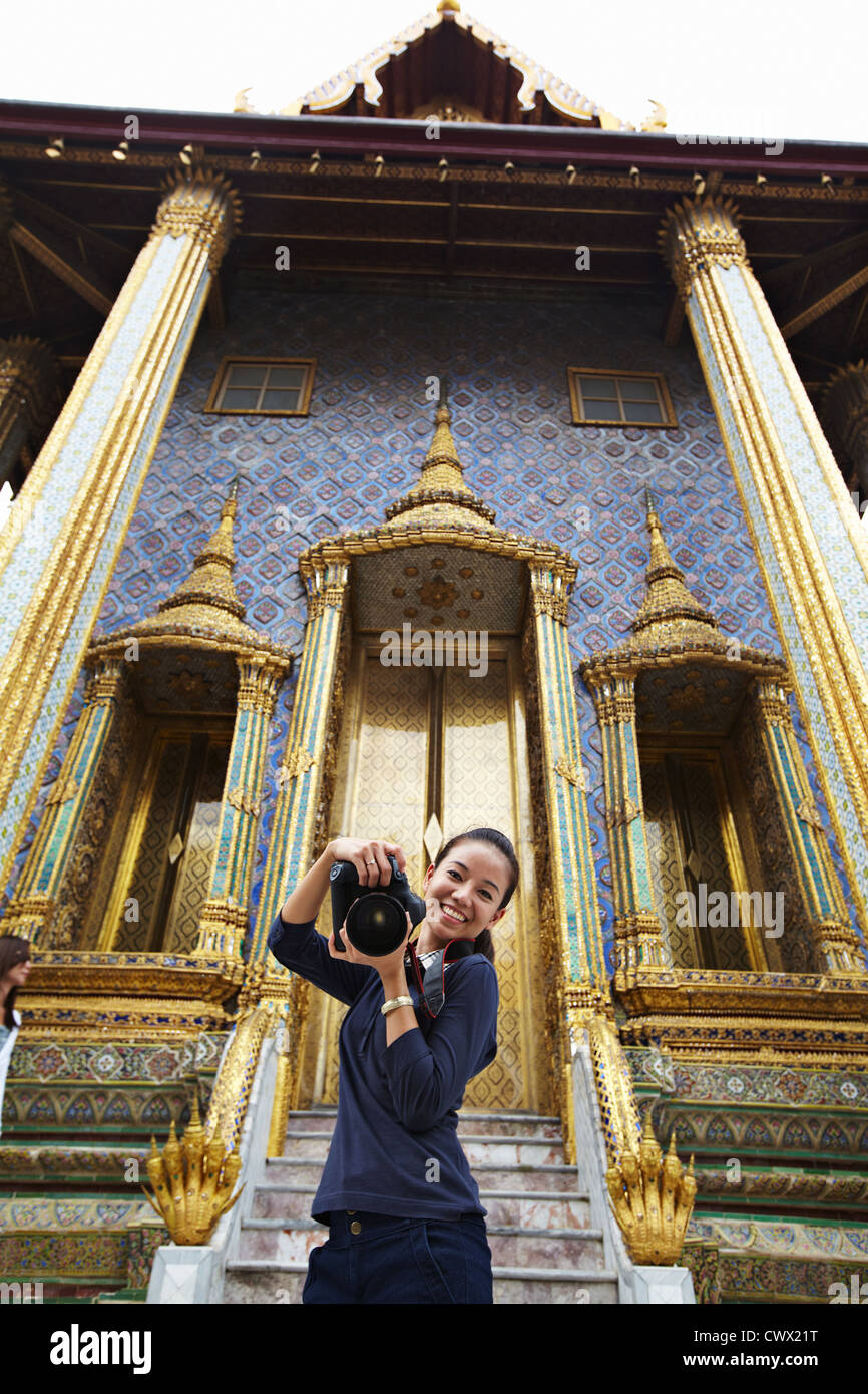 Woman taking pictures at ornate temple - Stock Image