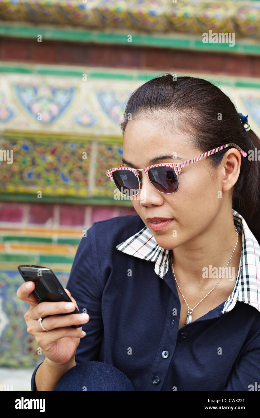 Woman using cell phone at ornate temple - Stock Image