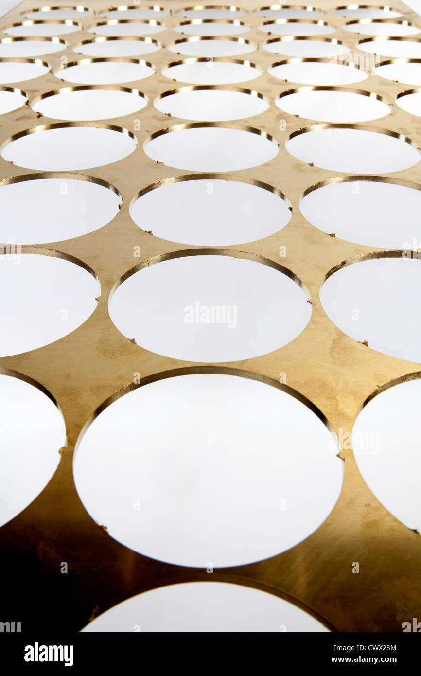 Brass sheet with round holes, brass scrap - Stock Image