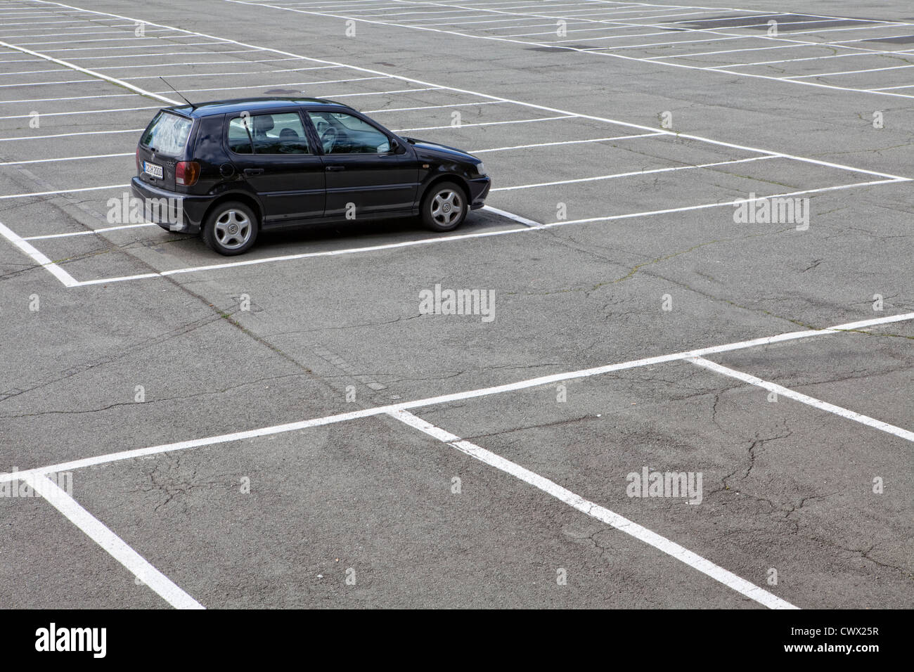 A single car parked on a large parking lot, concept image, parking spaces in Germany, Europe - Stock Image