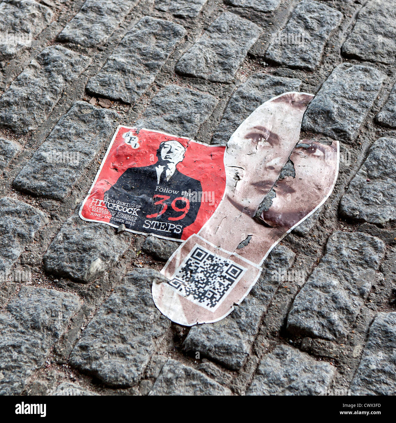 A sticker on paving on South Bank advertising the BFI's Alfred Hitchcock Festival, - Stock Image