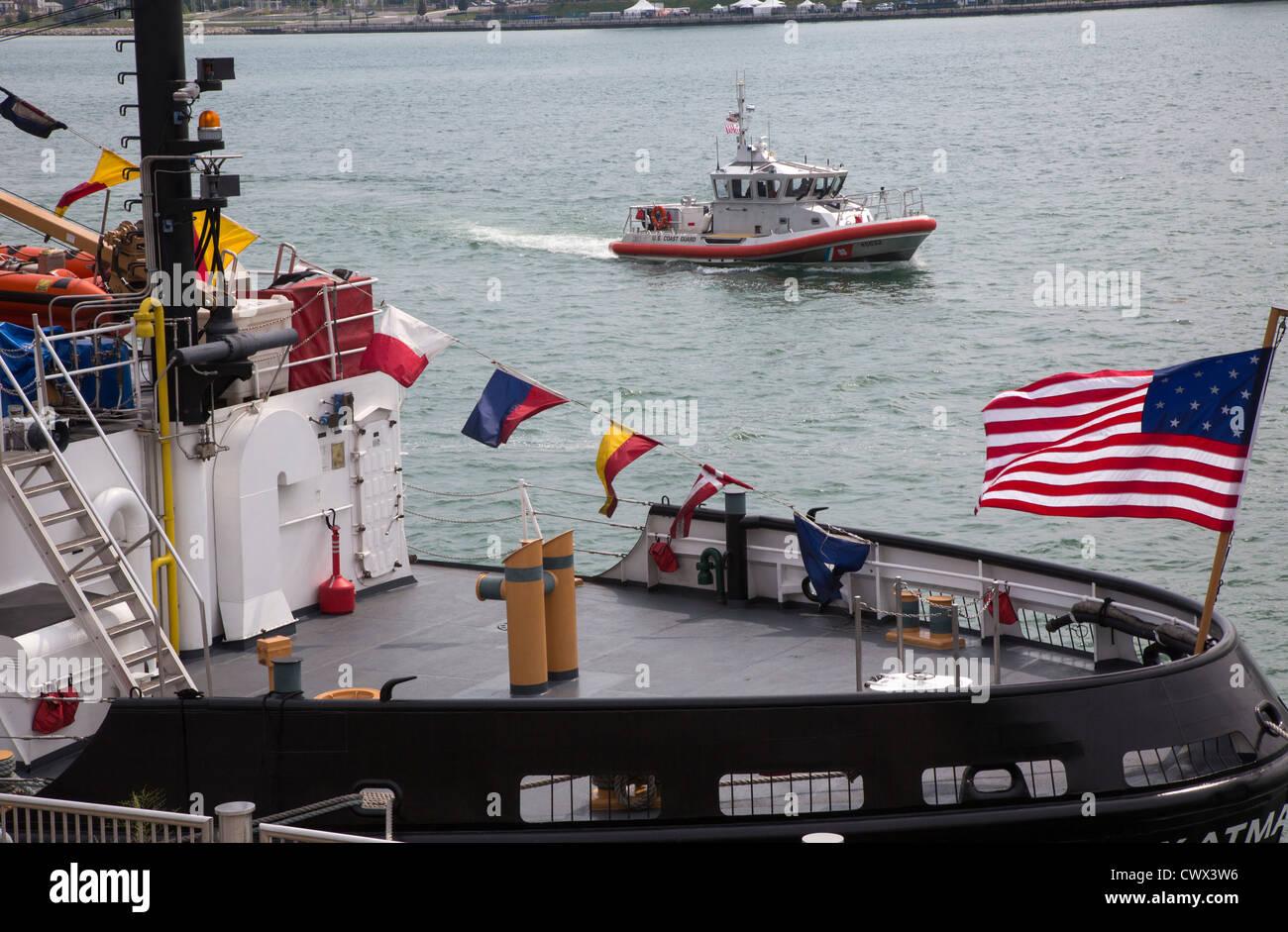 A small Coast Guard patrol boat passes the U.S. Coast Guard cutter Katmai Bay - Stock Image