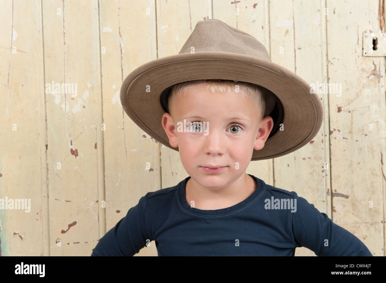 d4a36eac344ad little boy with cowboy hat against an old wooden door Stock Photo ...