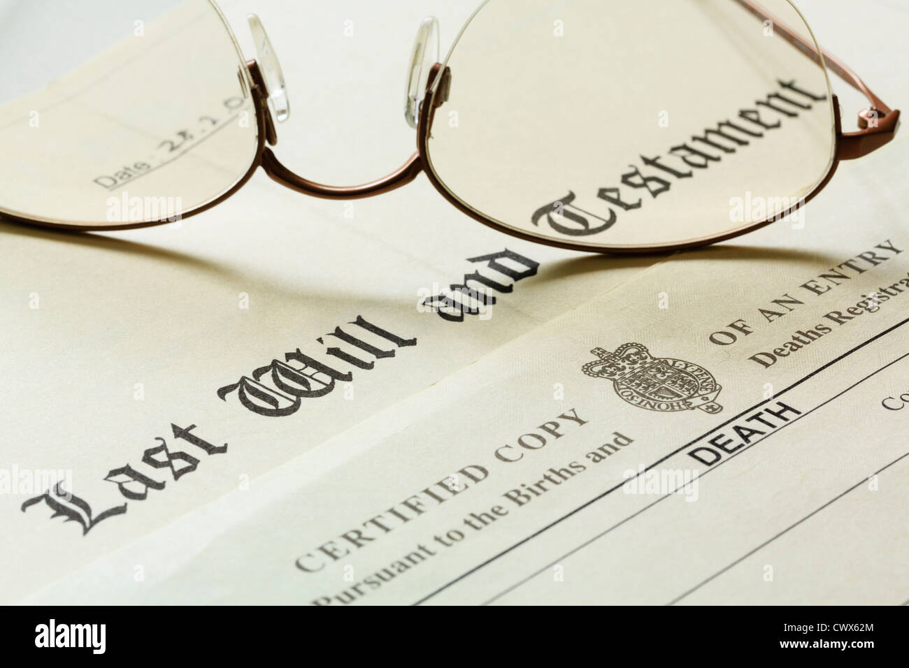 Last Will and Testament document with a Death Certificate and a pair of rose-tinted metal rimmed glasses. England - Stock Image