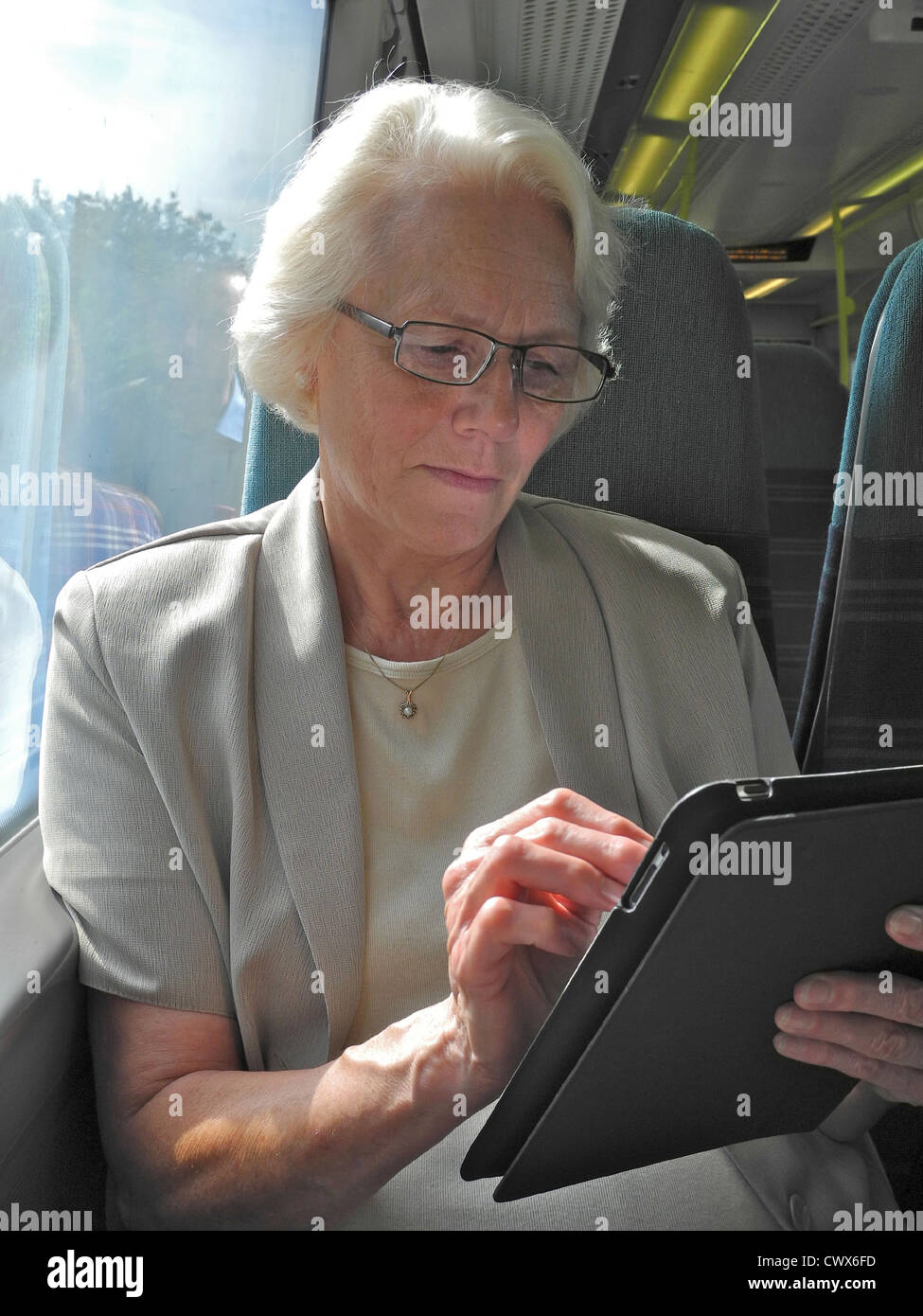 Mature woman using i-pad tablet computer while traveling. Tablet not identifiable. Stock Photo