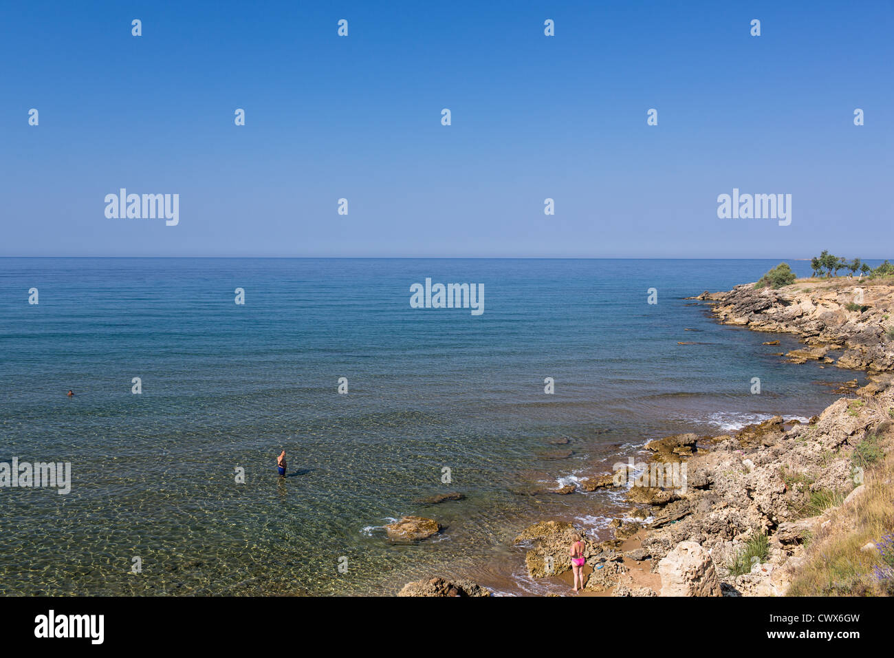 Tourists on an untamed coast in Agios Georgios, Corfu, Ionian Islands, Greece. - Stock Image
