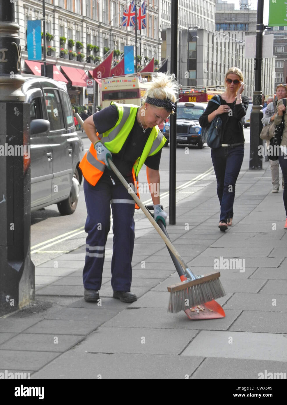 A London female woman lady street cleaner working on Buckingham Palace Road EDITORIAL USE ONLY - Stock Image