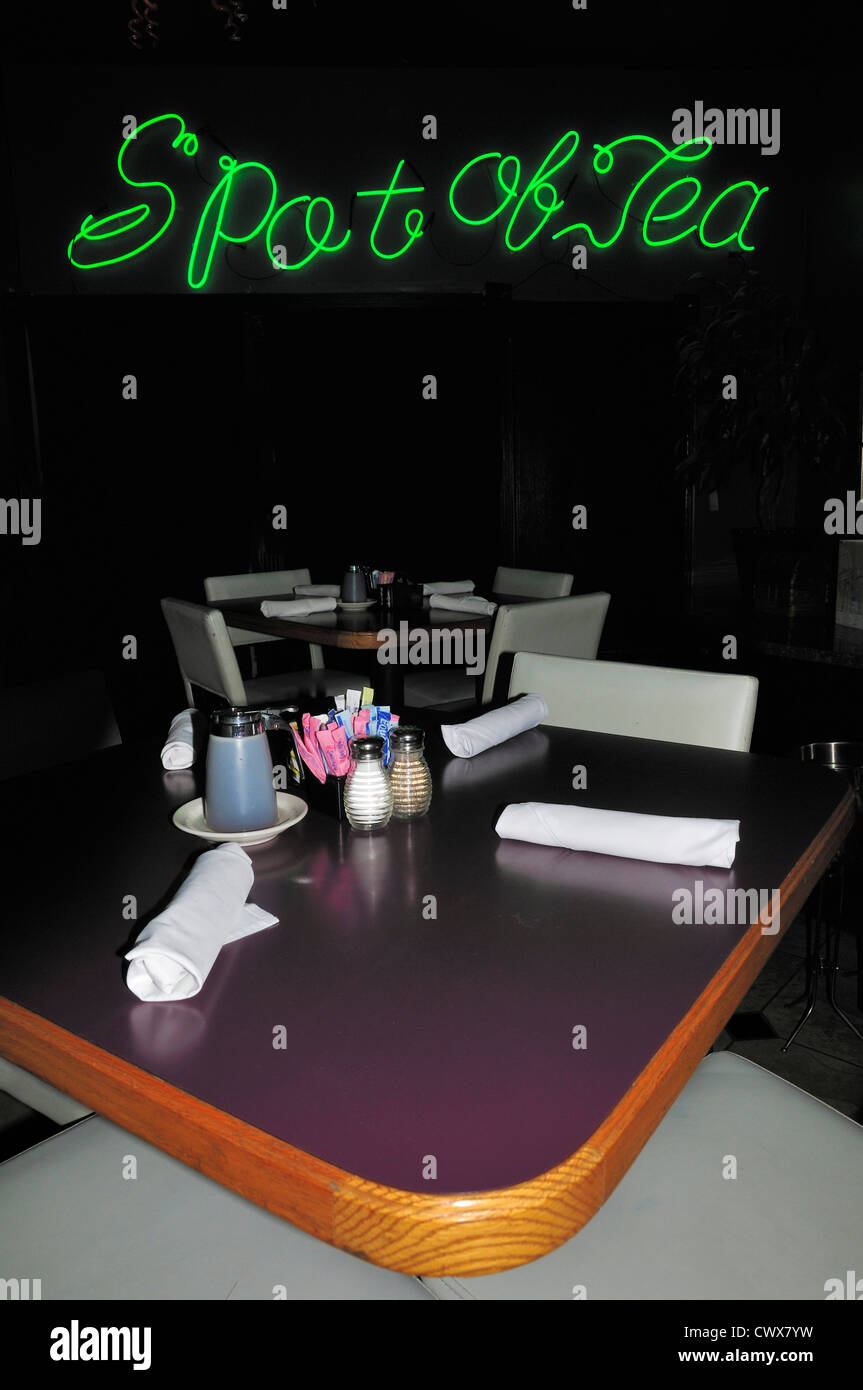 Table with setting and neon sign announcing the Spot of Tea restaurant, Mobile, Alabama - Stock Image