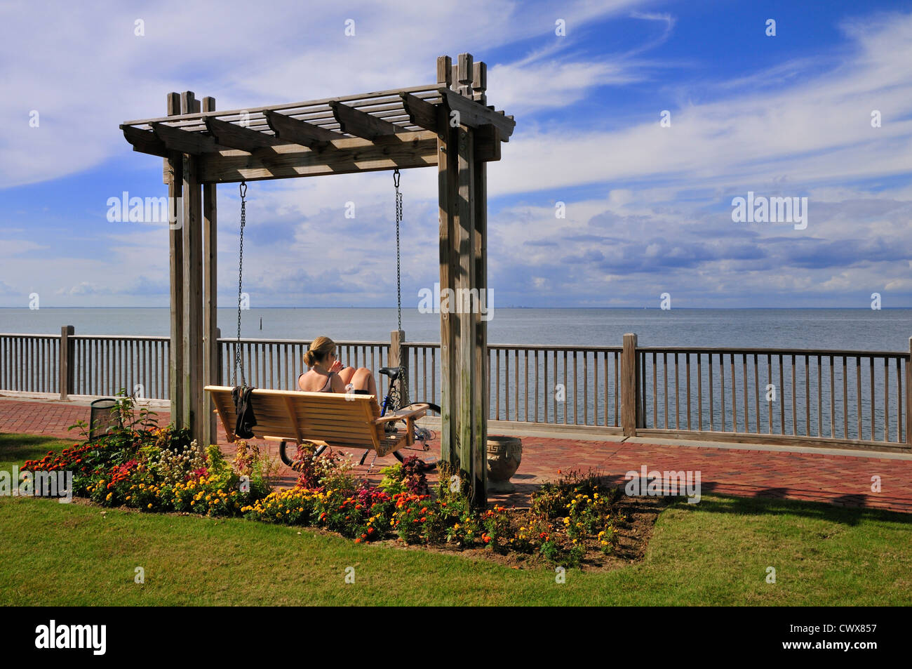A bicyclist rests on a hanging bench near the Grand Hotel at Point Clear, Alabama - Stock Image