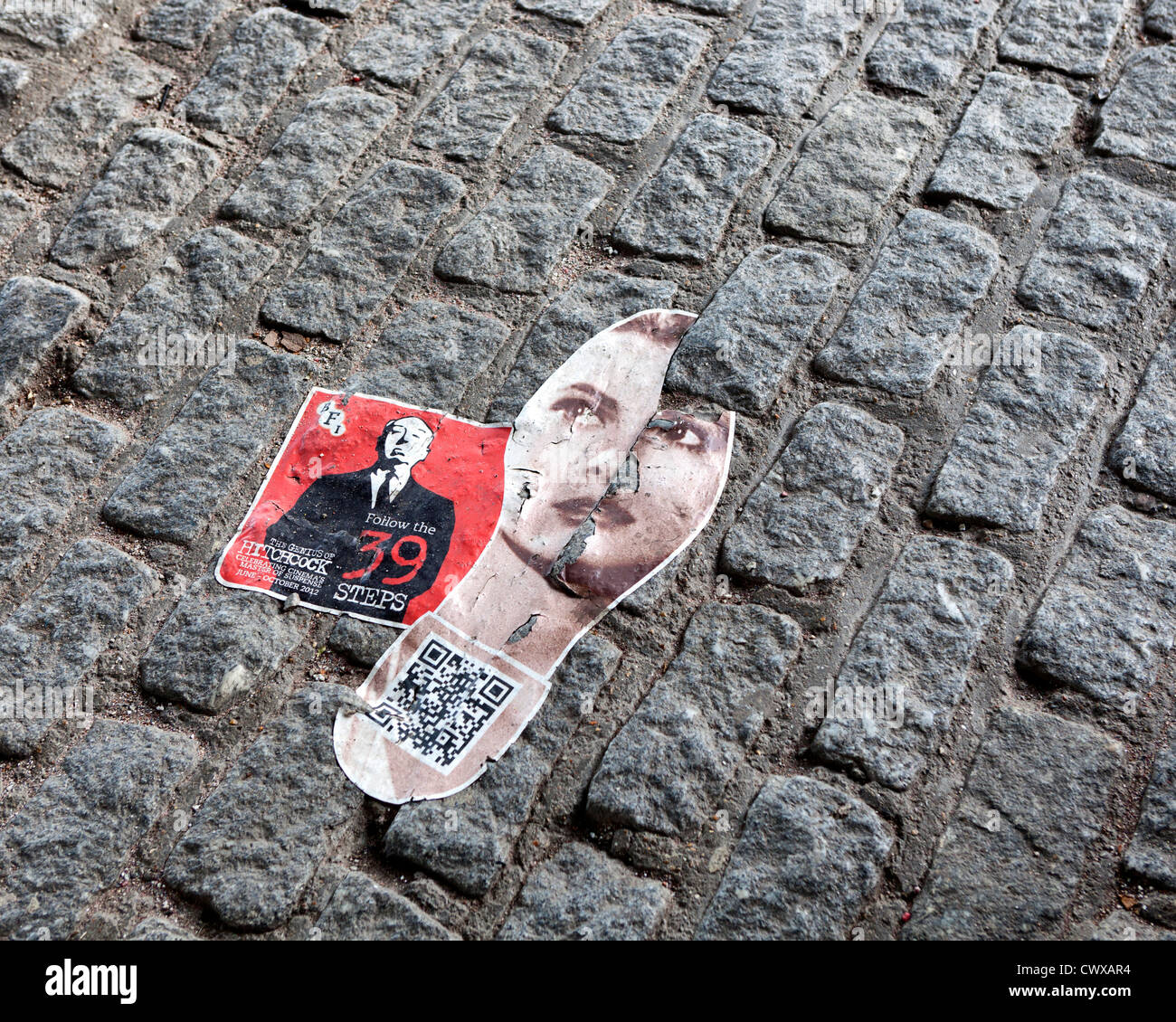 A sticker on paving stones on South Bank advertising the BFI's Alfred Hitchcock Festival, - Stock Image