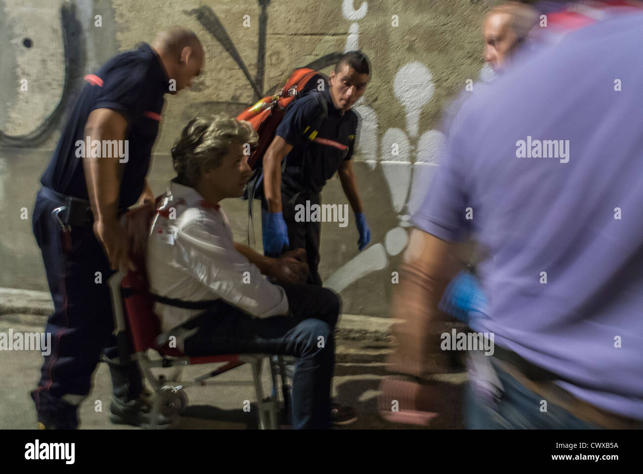 Perpignan, France, Man being Evacuated by French Firemen, Pompiers on Street at Night - Stock Image