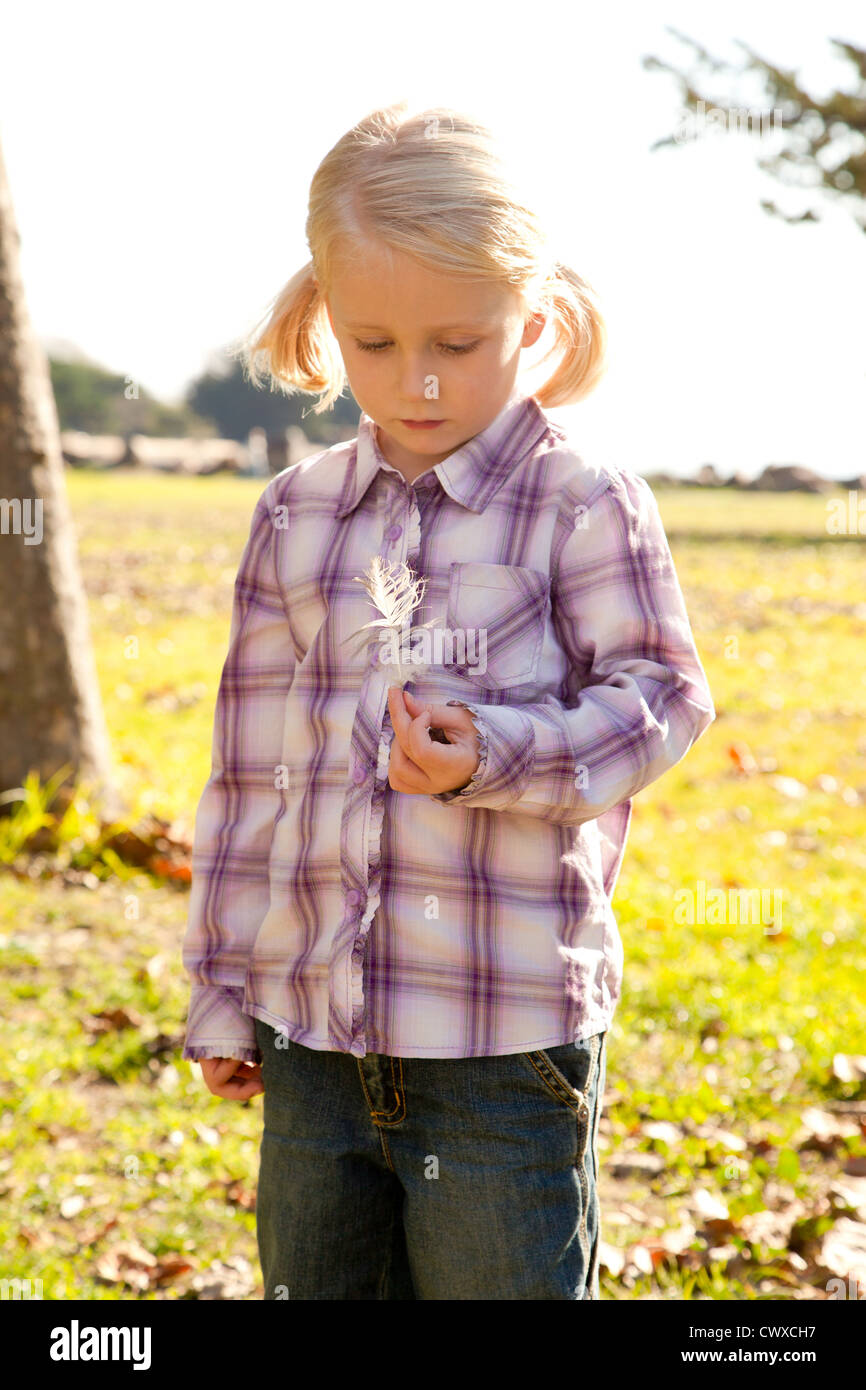 Small blond girl in a plaid shirt is holding a feather. - Stock Image