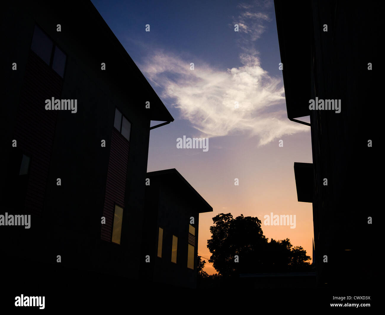 Silhouettes of townhouse condos against a colorful sunset - Stock Image