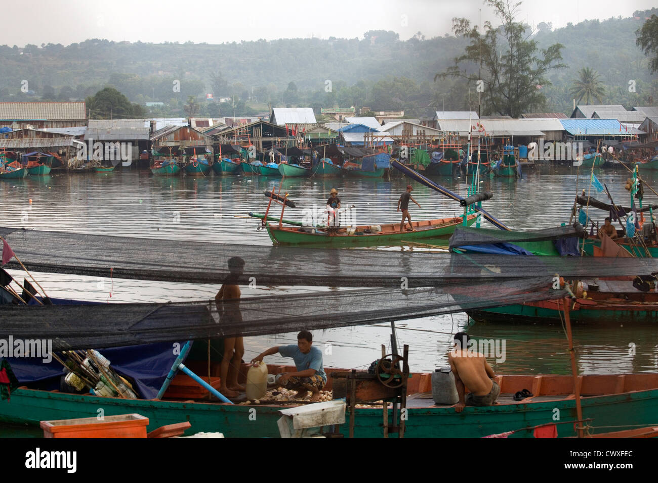 A busy fishing village with wooden boats & homes on stilts, Sihanoukville, Cambodia, South East Asia - Stock Image