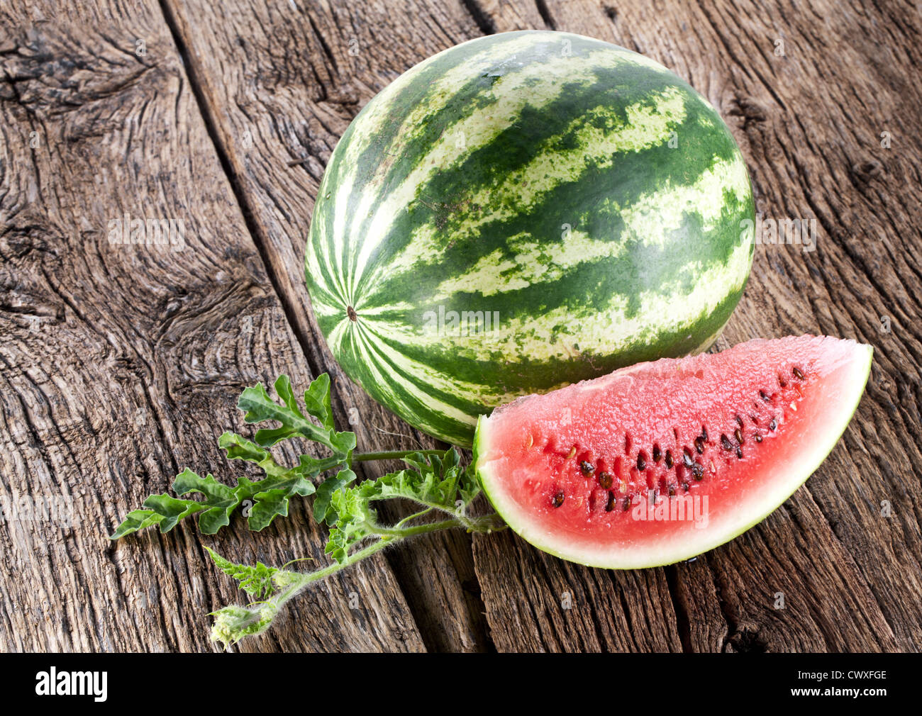 Watermelon with a slice and leaves on a wooden table. - Stock Image