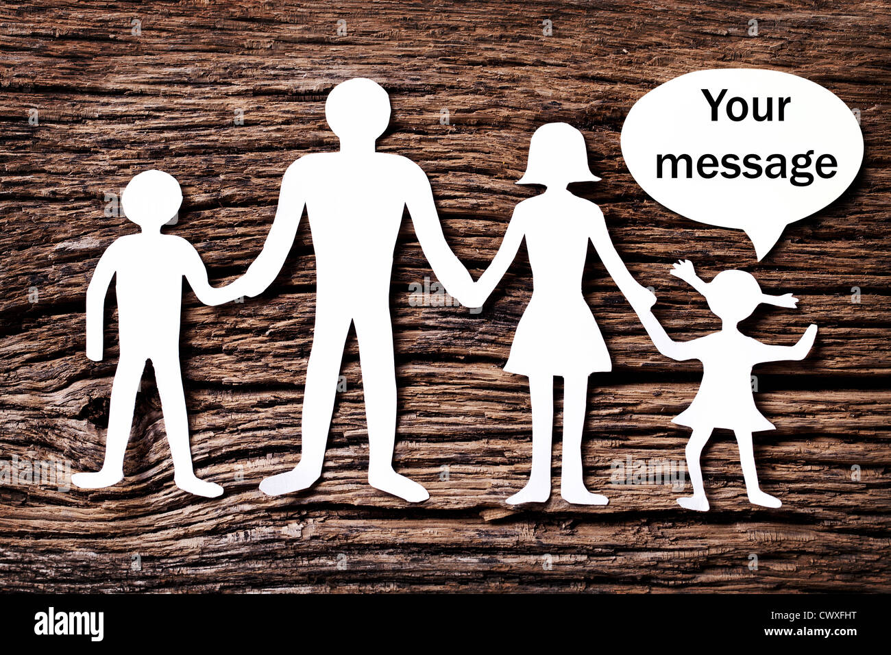 Cardboard figures of the family on a wooden table. The symbol of unity and happiness. Above the daughter bubble, - Stock Image