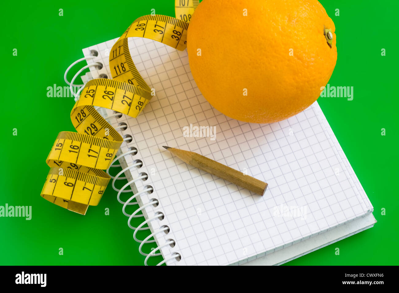 Writing in a diet and nutrition journal with orange to the side - Stock Image