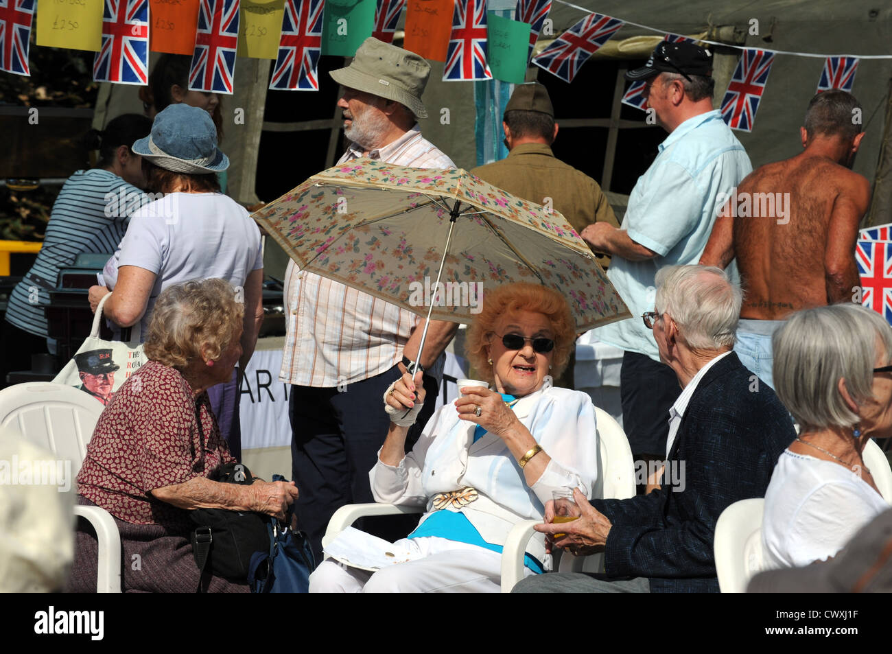 This lady keep the sun off with an umbrella at The Blind Veterans UK annual Vintage Fair in Ovingdean today - Stock Image