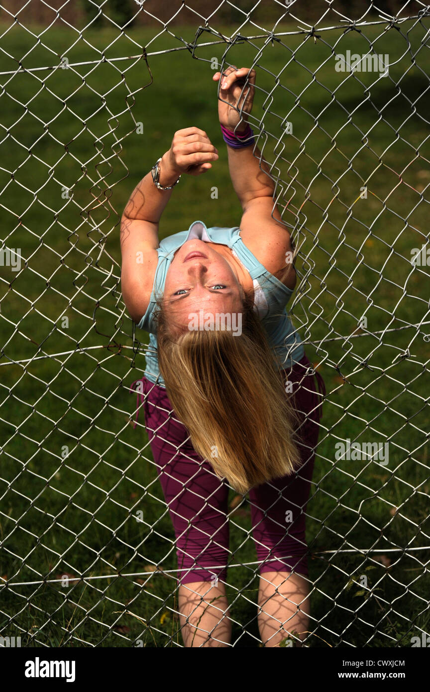 Girl upside down crossing a broken wire fence Stock Photo