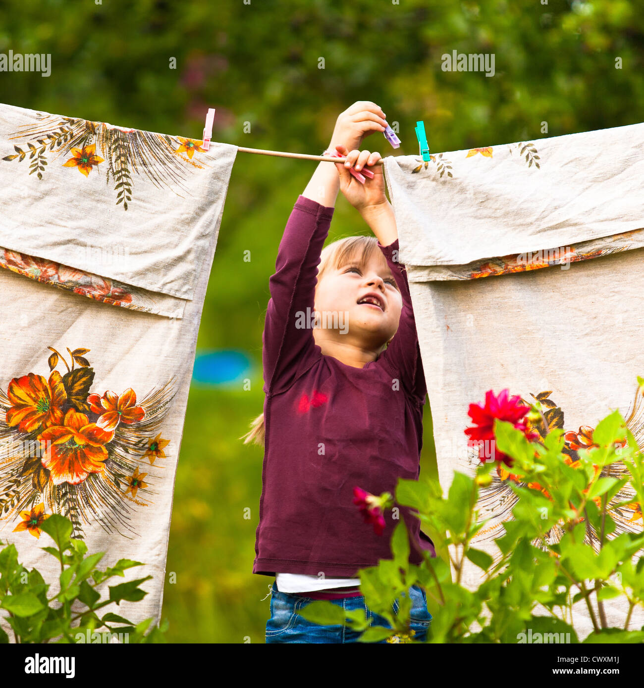 Sweet five-year girl with clothespin and the clothesline - Stock Image