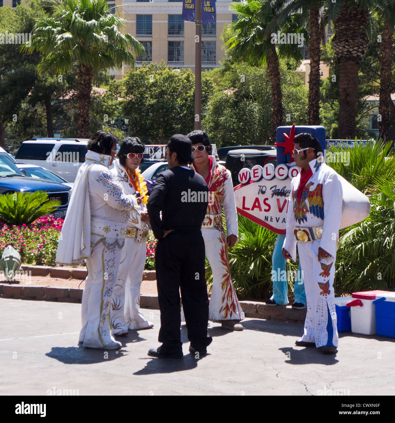 A group of Elvis Presley impersonators talk with a hotel bellboy on The Strip in Las Vegas,Nevada,USA. - Stock Image