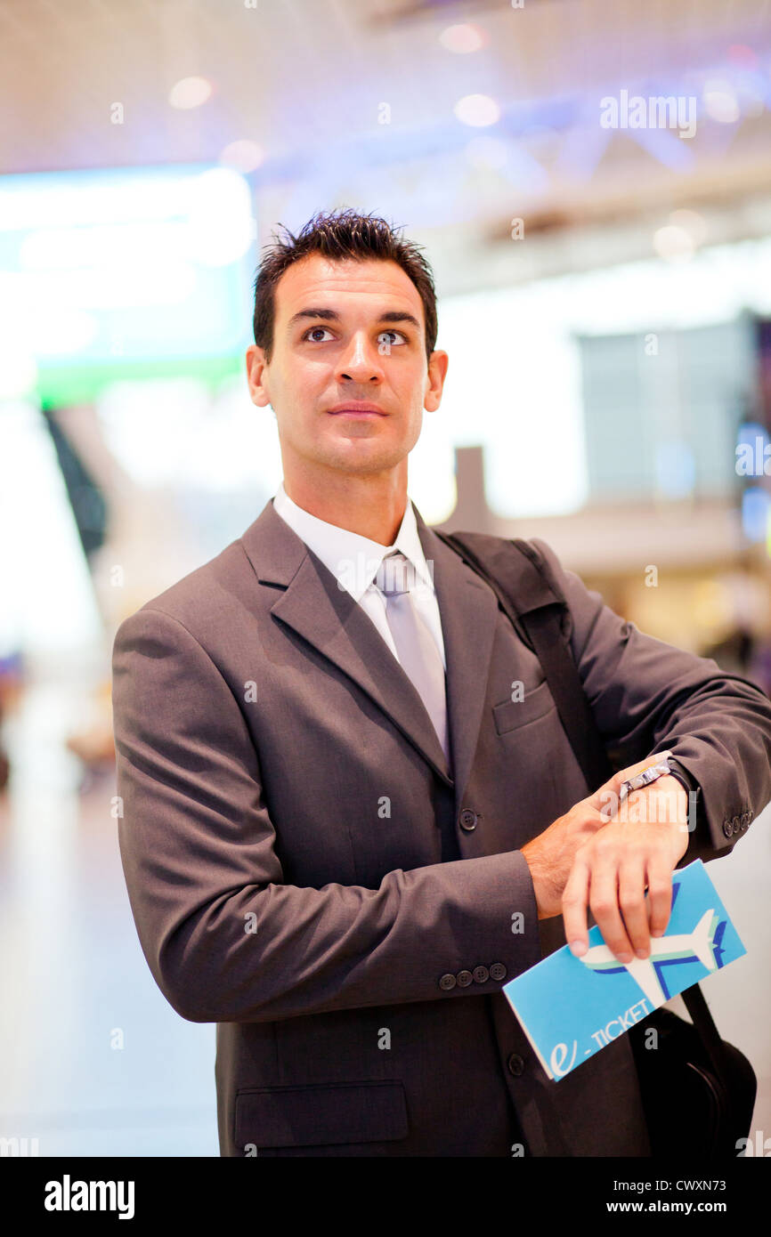 handsome businessman checking flight departure time at airport Stock Photo