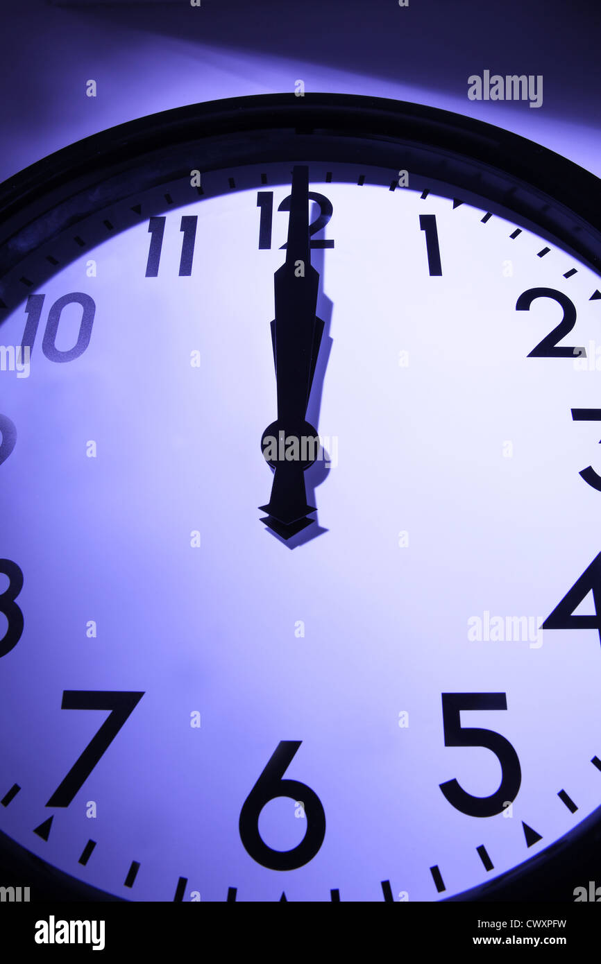 A clock with hands pointing to mid night. - Stock Image