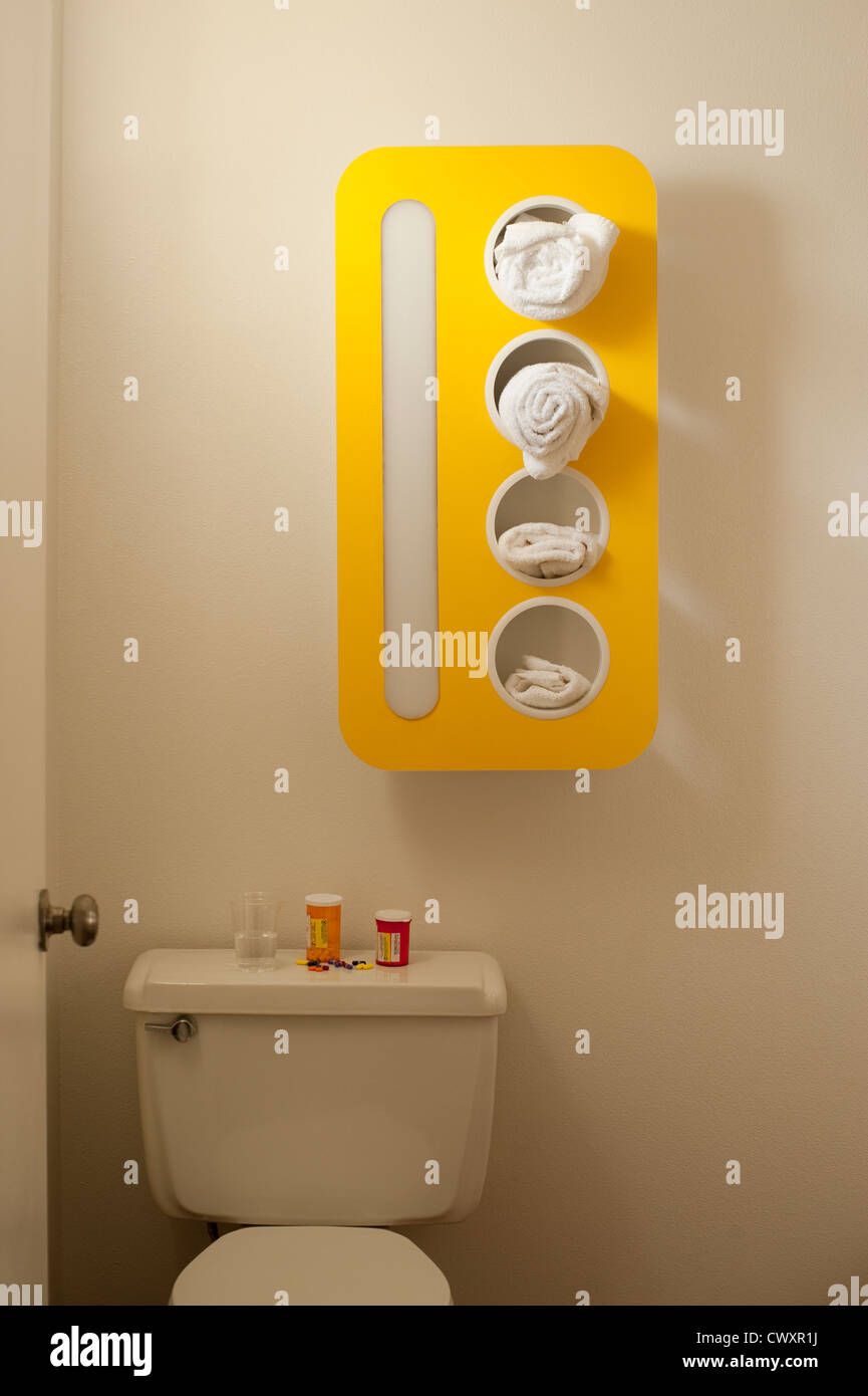Bathroom with towel rack and pill bottles on back of toilet Stock ...
