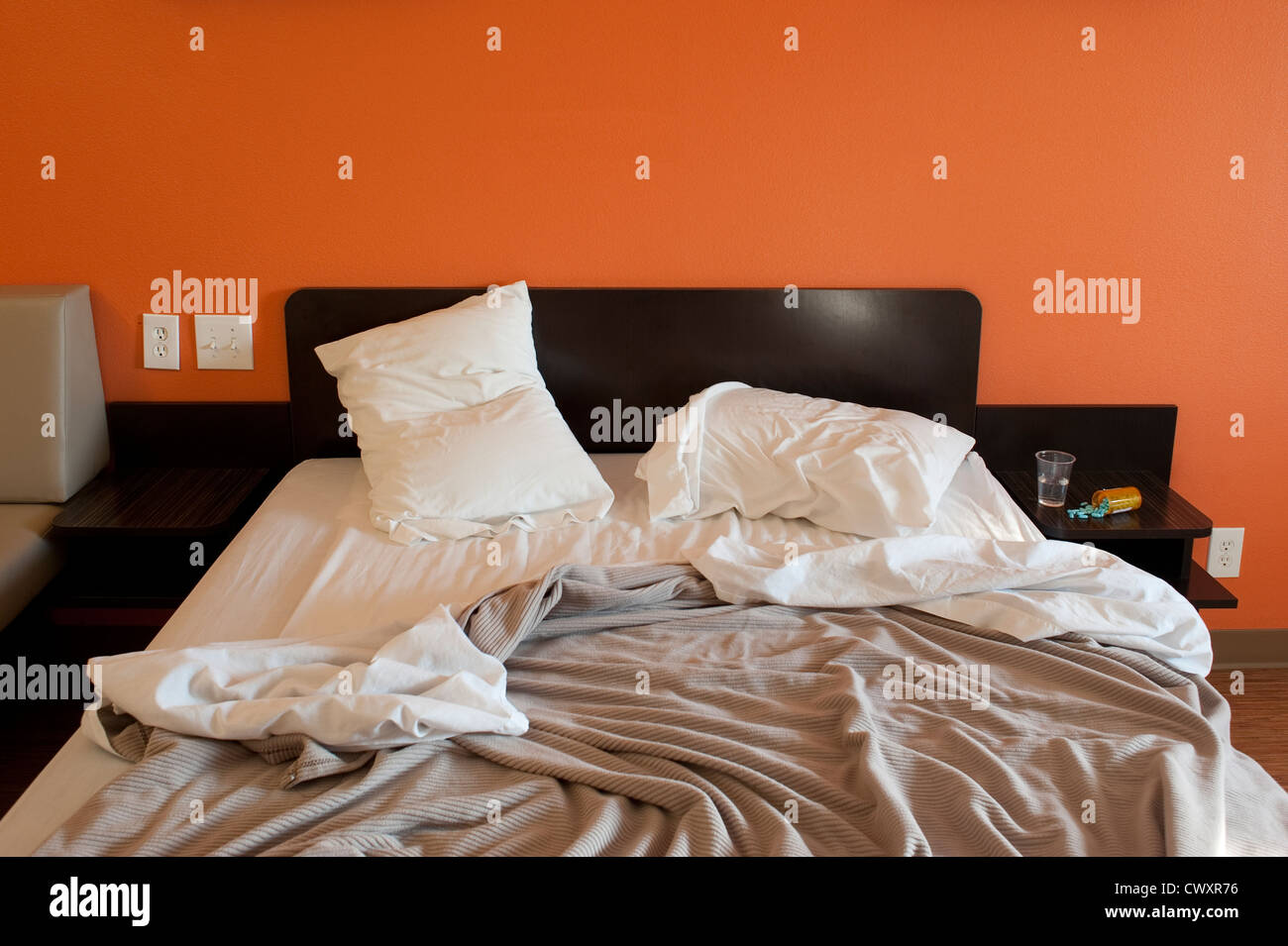 Motel room with bed and medications pill bottles on side table and messy bed - Stock Image