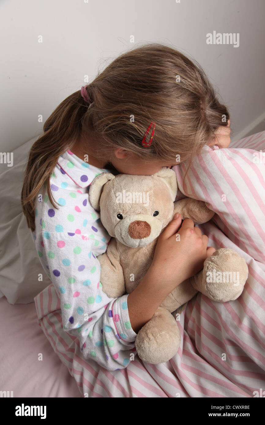 Young girl in bed cuddling a teddy bear. - Stock Image