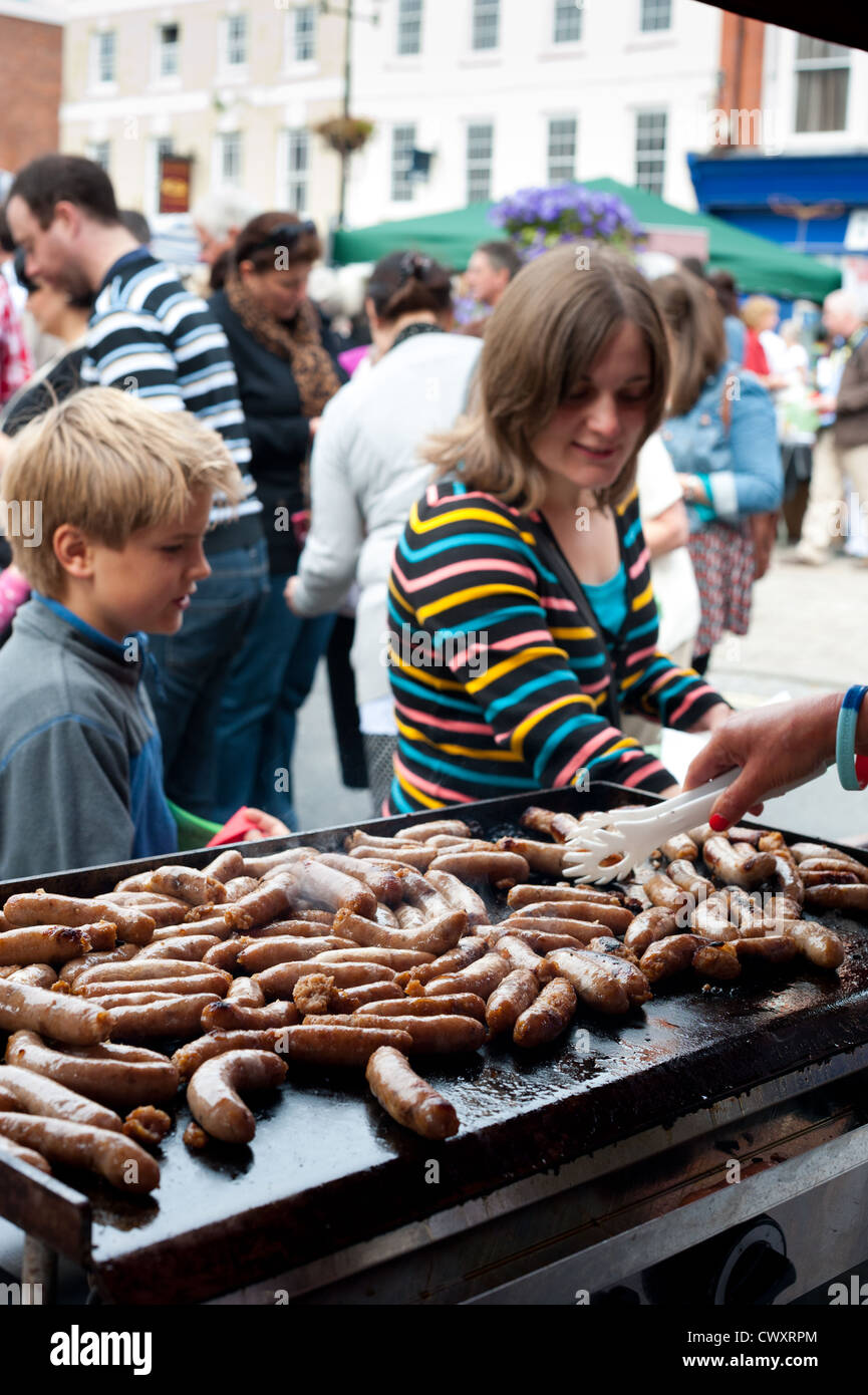 Sausages cooking on a griddle during the Ludlow 2012 Food Festival - Stock Image