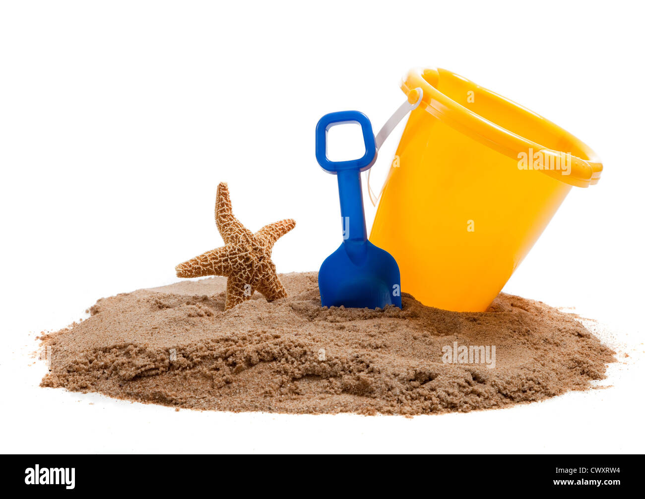 A Yellow Bucket and blue shovel on the beach with a starfish - Stock Image