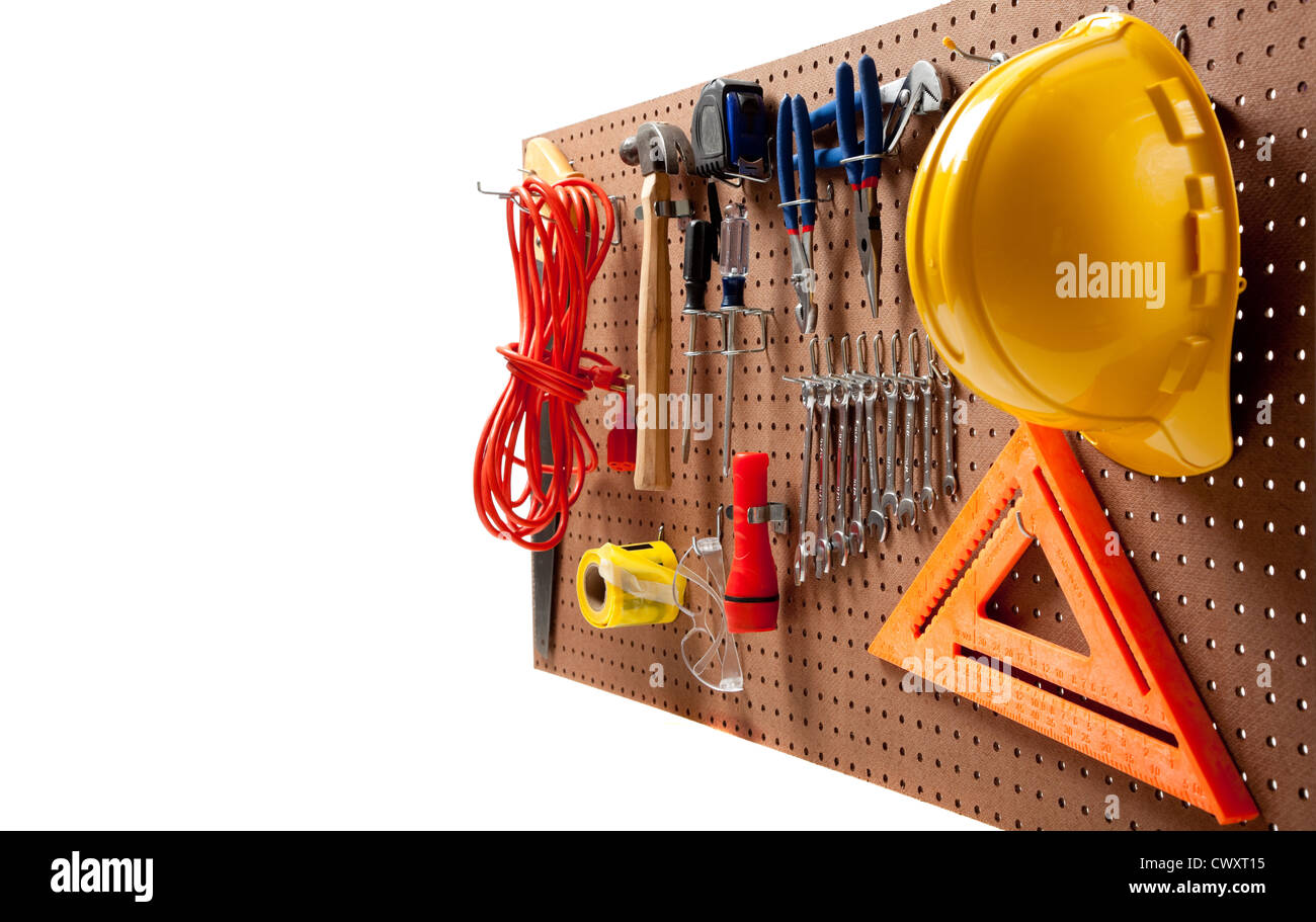 Peg board with hardhat, extension cord, flashlight, hammer, screw driver, caution tape, carpenter's square and - Stock Image