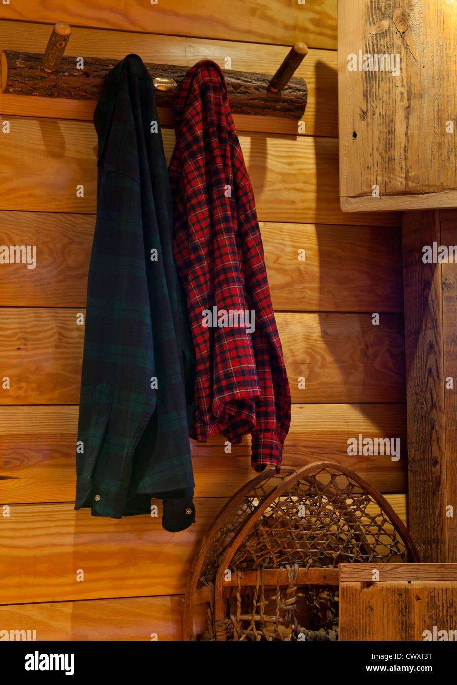 Plaid shirts hanging on log home wall - Stock Image
