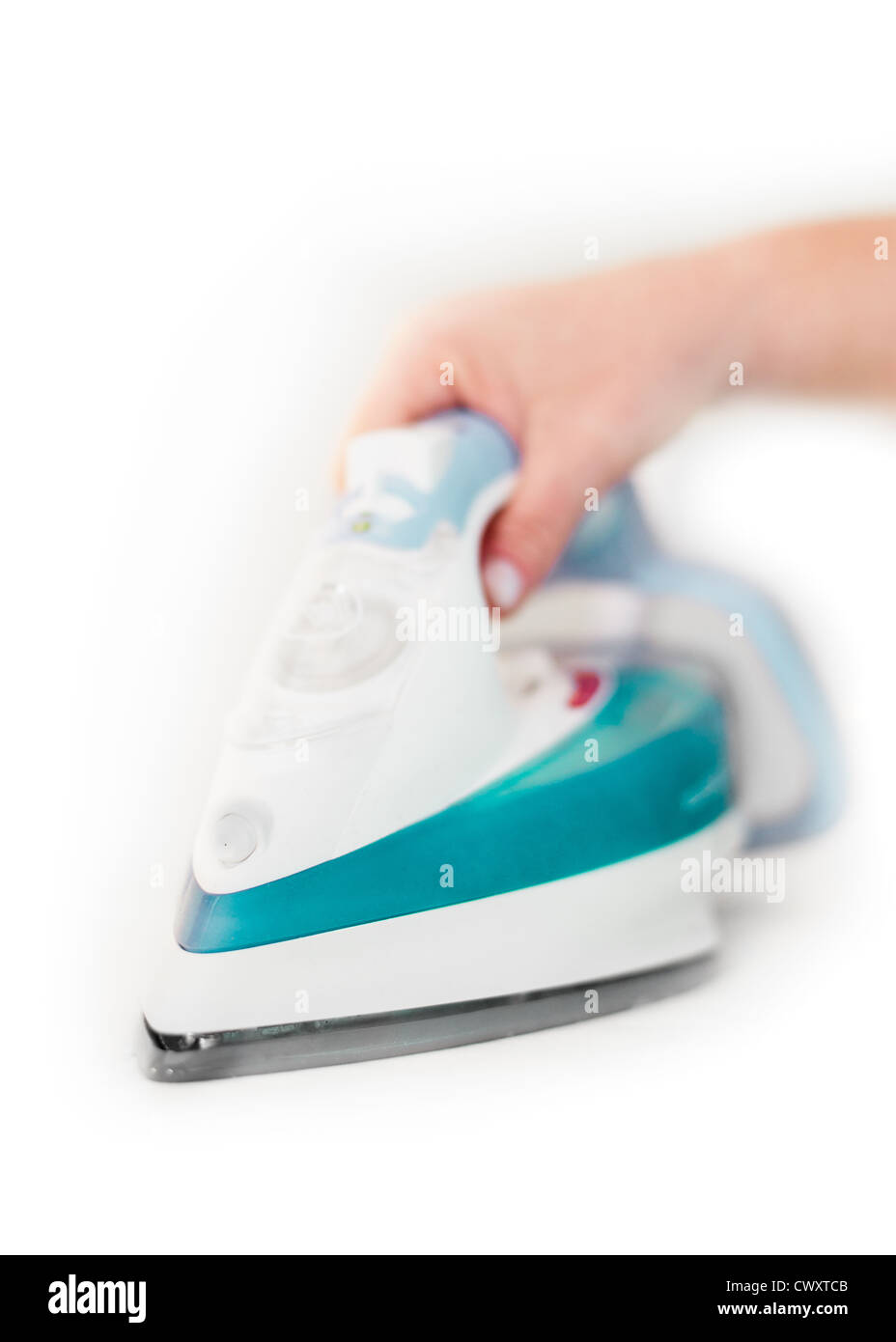 A woman's hand , using a modern electric steam iron - Stock Image