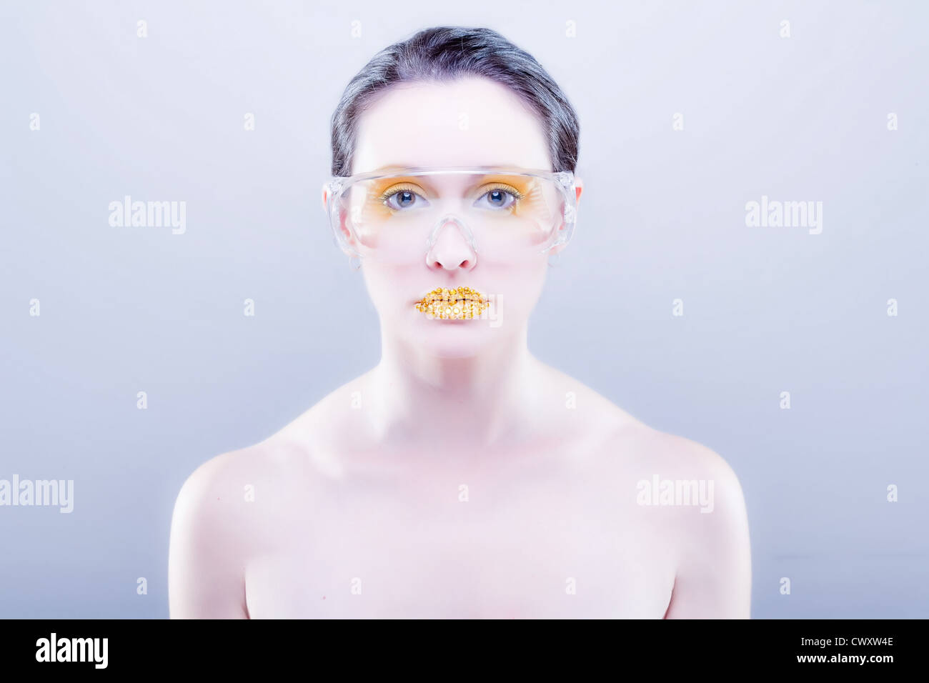 Young caucasian woman with gold fashion makeup wearing clear glasses and gold diamonties on her lips - Stock Image