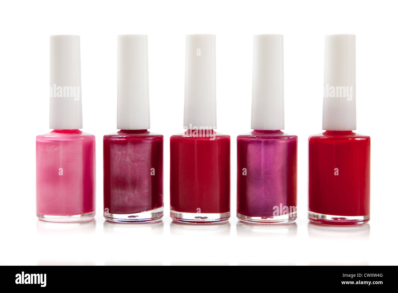 71901f0a82c4 A row of various shades of red fingernail polish on a white background