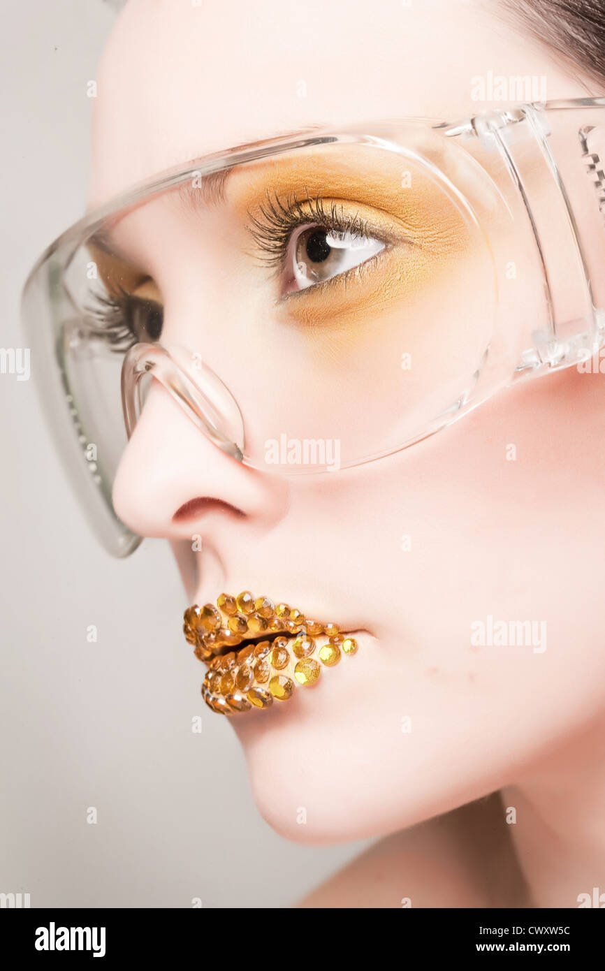 Young caucasian woman with gold fashion makeup wearing clear glasses and gold diamonties on her lips Stock Photo